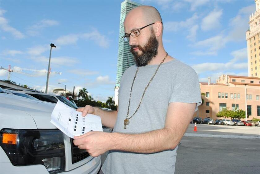 """Steve Parker, artista creador de """"Traffic Jam"""" (Embotellamiento), lee las indicaciones de la música creada con los autos hoy, 3 de diciembre de 2016, en Miami, Florida. La reconocida fama que tiene el tráfico de Miami ya cuenta con música de fondo, la """"Sinfonía I-95"""", ideada por el artista Steven Parker y quien hoy presentó en esta ciudad su singular creación hecha a base de ruidos de vehículos. La acción artística """"Traffic Jam"""" (Embotellamiento) invitó a los participantes, más de 50 conductores de vehículos, a formar parte de esta particular orquesta, en la que antes que conocimientos musicales hacía falta seguir las instrucciones para elaborar una melodía compuesta por sonidos de motor, bocinazos, parabrisas y las luces intermitentes. EFE"""