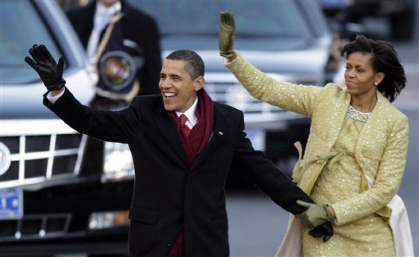 FILE - This Jan. 20, 2009 file photo shows President Barack Obama and first lady Michelle Obama waving as they walk down Pennsylvania Avenue on their way to the White House in Washington, after taking the presidential oath. In a reversal from four years ago, President Barack Obama will accept unlimited sums of money from corporations and individuals to pay for events surrounding his Inauguration, a spokeswoman said Friday. (AP Photo/Alex Brandon, File)