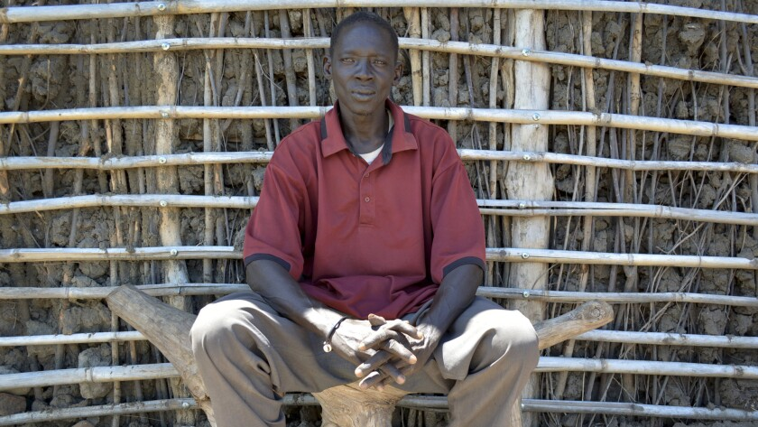 Luko Loku, a South Sudanese cattle herder from the Mundari tribe, sits outside his one-room thatched home.