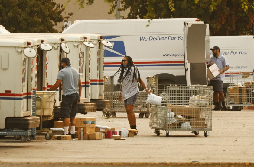 People with carts loading mail trucks.
