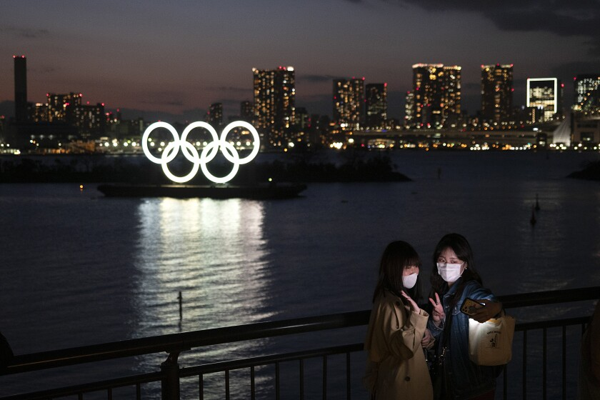 En esta fotografía del 12 de marzo de 2020, dos mujeres se toman una fotografía con los aros olímpicos