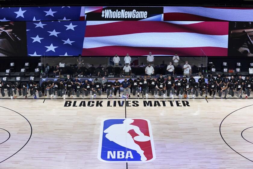 Jugadores y entrenadores de los Pelicanos de Nueva Orleans y del Jazz de Utah se hincan
