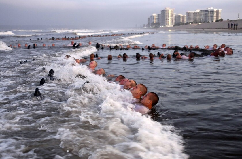 """SEAL candidates participating in """"surf immersion"""" during Basic Underwater Demolition/SEAL (BUD/S) training in Coronado"""