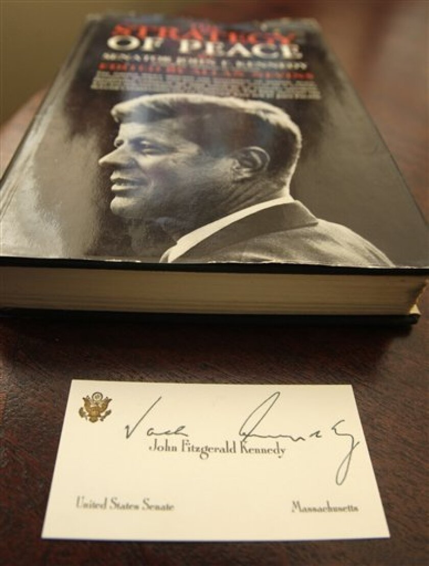 """A U.S. Senate business card with then Sen. John Fitzgerald Kennedy's name inscribed and a purported autograph written on the card as """"Jack Kennedy"""" is displayed near the 1960 book in Little Rock, Ark., Monday, Nov. 8, 2010, where the card was found between the pages the books's owner says. (AP Photo/Danny Johnston)"""