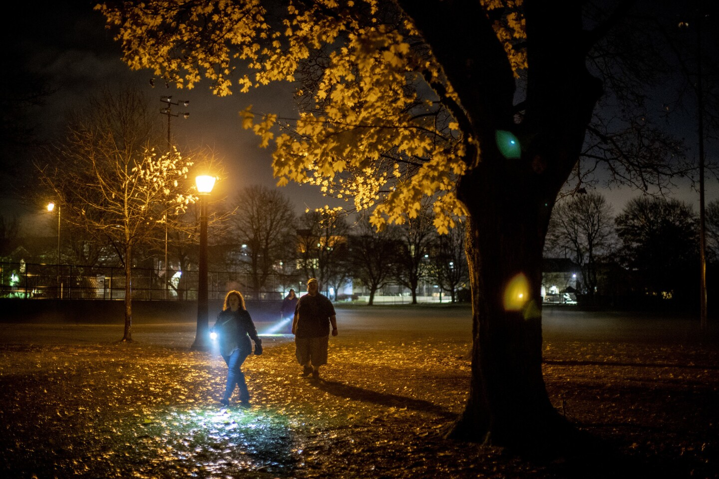 Angela Todd, left, and Benjamin Kerensa, members of the Montavilla Initiative citizens group, patrol Montavilla Park by flashlight in Portland, Ore.