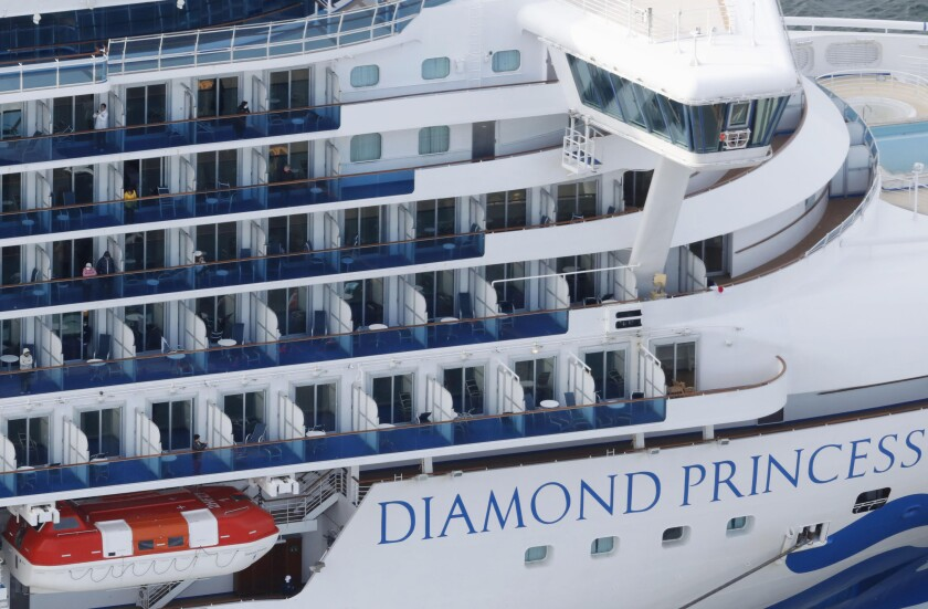 Some passengers are seen on the Diamond Princess as the cruise ship is anchored at Yokohama Port for supplies replenished in Yokohama, south of Tokyo, Thursday, Feb. 6, 2020. The 3,700 people on board faced a two-week quarantine in their cabins. (Kenzaburo Fukuhara/Kyodo News via AP)