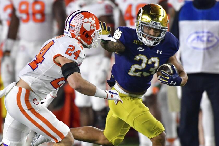 Notre Dame's Kyren Williams wards off Clemson safety Nolan Turner on a touchdown run Nov. 7, 2020.