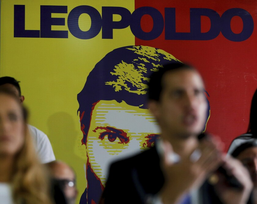 FILE - In this Feb. 18, 2019 file photo, Venezuela's self-proclaimed interim president Juan Guaido speaks during a news conference at the Popular Will party headquarters, backdropped by a banner featuring party founder and opposition leader Leopoldo Lopez, in Caracas, Venezuela. Venezuela's government-stacked Supreme Court ordered the takeover of Popular Will Tuesday, July 7, 2020, the latest in a series of moves against President Nicolas Maduro's critics before upcoming legislative elections. (AP Photo/Fernando Llano, File)