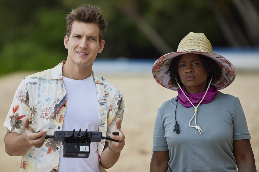 A man holding a drone remote control stands on a beach next to a woman wearing a straw hat.