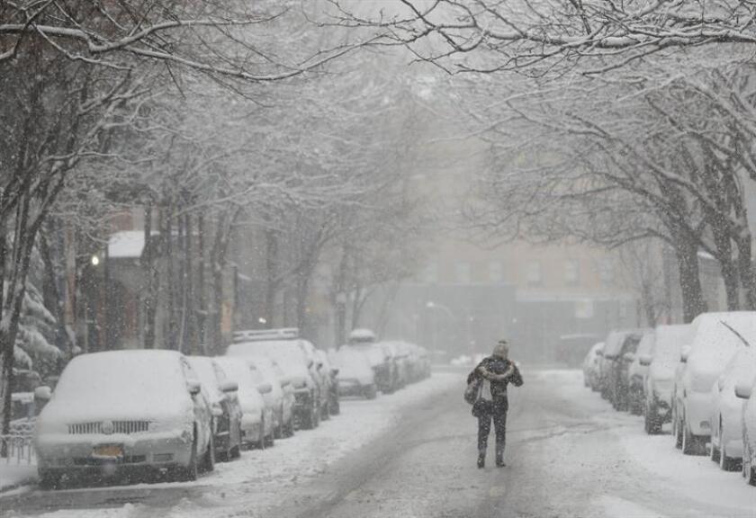 Una mujer camina por la carretera durante una tormenta de nieve un día después del comienzo de la primavera, en Nueva York (Estados Unidos). EFE