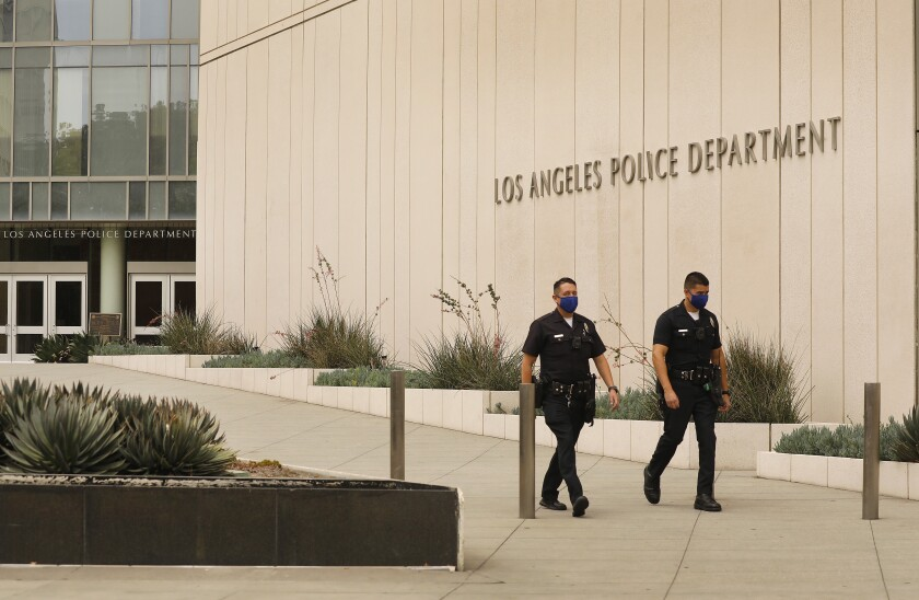 Officers march by the Los Angeles Police Department headquarters in downtown L.A.