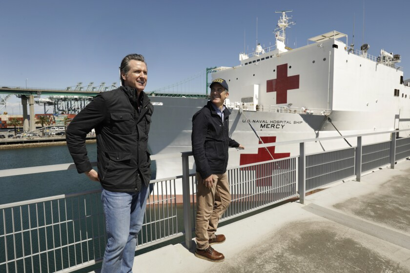 Gov. Gavin Newsom, left, and Los Angeles Mayor Eric Garcetti, stand in front of the hospital ship USNS Mercy that arrived into the Port of Los Angeles on Friday. Both Newsom and Garcetti have announced a delay on evictions for tenants who cannot pay their rent because of the pandemic outbreak.