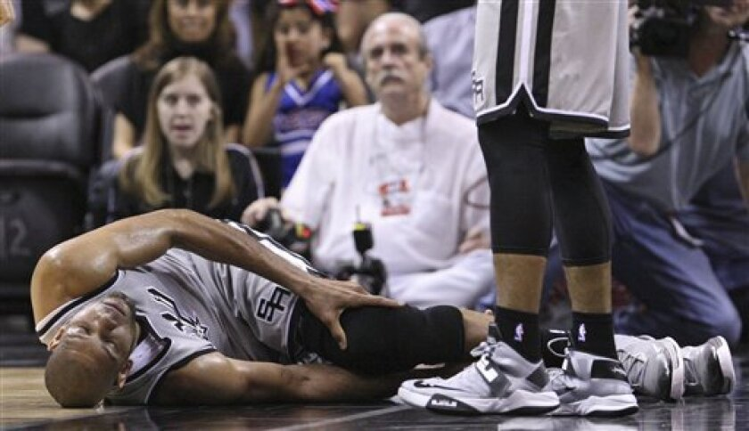San Antonio Spurs' Tim Duncan lies on the floor after being injured on a play during the first half against the Washington Wizards during an NBA basketball game Saturday, Feb. 2, 2013, in San Antonio. The Spurs said via Twitter that Duncan sprained his right ankle and left knee and would not return