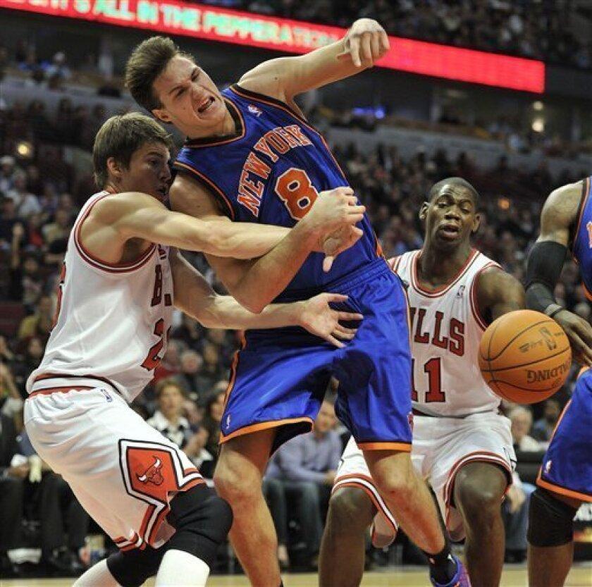 Chicago Bulls' Kyle Korver, left, knocks the ball away from the New York Knicks' Danilo Gallinari (8) during the first half of an NBA basketball game Thursday, Nov. 4, 2010, in Chicago. (AP Photo/Jim Prisching)