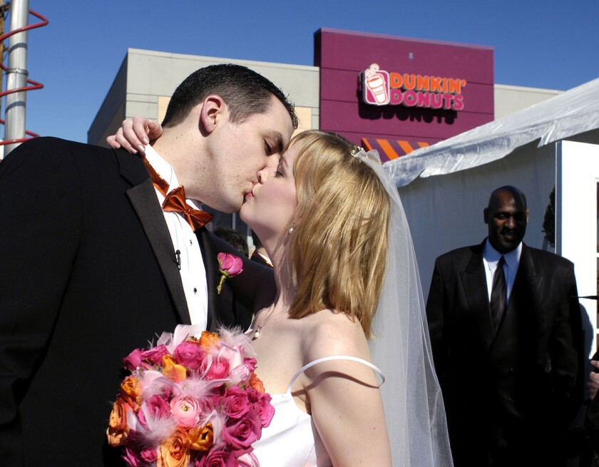 PHILADELPHIA - FEBRUARY 11: Jeff Dewald and Margaret Neary kiss after their wedding at Dunkin' Donuts February 11, 2005 in Philadelphia, Pennsylvania. The couple won an essay contest in which they wrote about their proposal and won an all expense-paid wedding at Dunkin' Donuts along with a honeymoon trip. (Photo by William Thomas Cain/Getty Images)