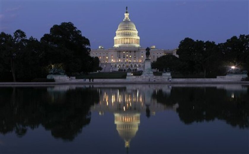 The U.S. Capitol in Washington is illuminated as the debt-limit stalemate continues Saturday night, July 30, 2011.  (AP Photo/J. Scott Applewhite)