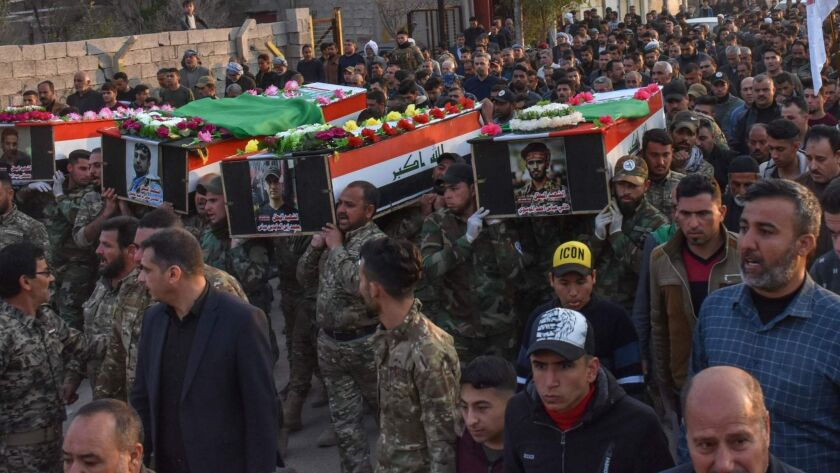 Iraqi paramilitary members carry the coffins of fellow fighters during a funeral Thursday in their hometown of Tuz Khurmatu. They were killed a day earlier in an ambush outside Mosul.