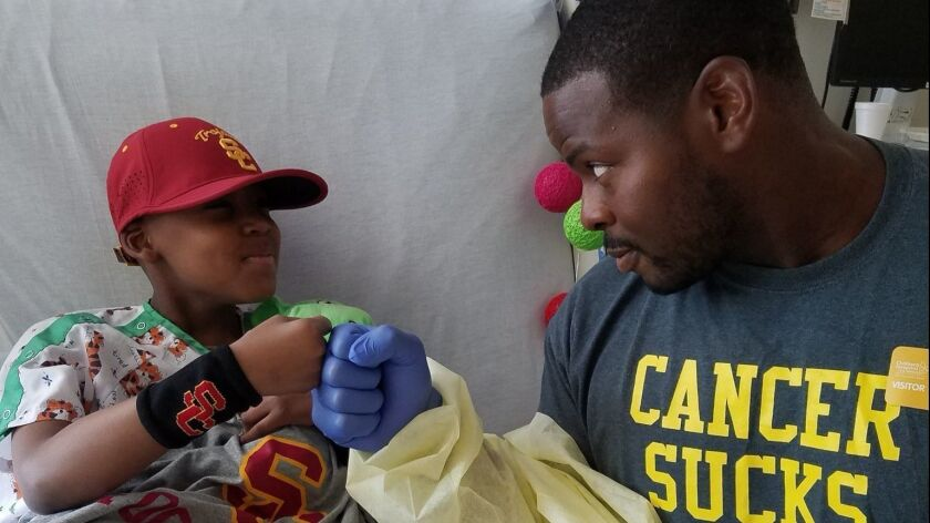 Kenechi Udeze, right, USC's defensive line coach and a leukemia survivor, visits Taylor Hammond at Los Angeles Children's hospital in July 2016. Hammond died of leukemia in December.