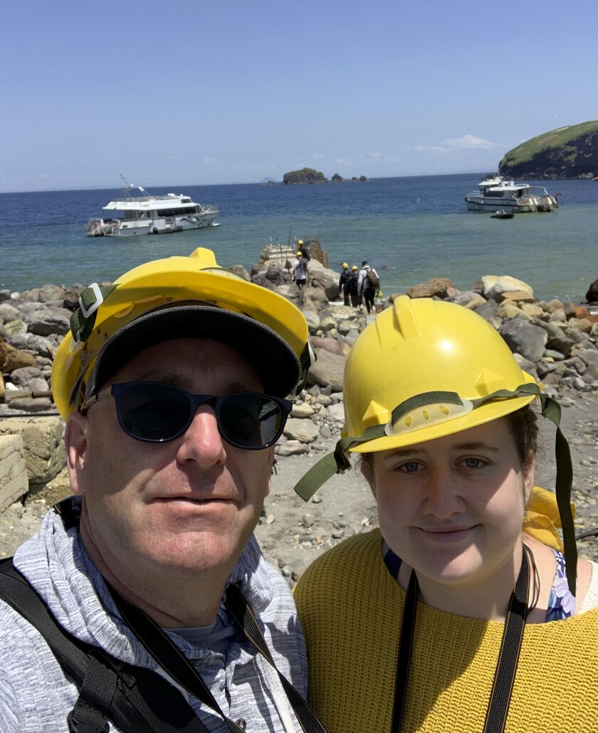 In this Monday, Dec. 9, 2019, photo provided by Lillani Hopkins, Lillani Hopkins pictured with her father Geoff prior to the eruption on White Island off the coast of Whakatane, New Zealand. Lillani Hopkins was feeling seasick and keeping her eyes trained on the open water as her tour boat swung around for a last view of the White Island volcano on Monday afternoon, Dec 9, 2019. Suddenly people started gasping and then her dad whacked her, telling her to turn around. The eruption had been so silent she hadn't heard it over the noise of the boat's engines. (Lillani Hopkins via AP)