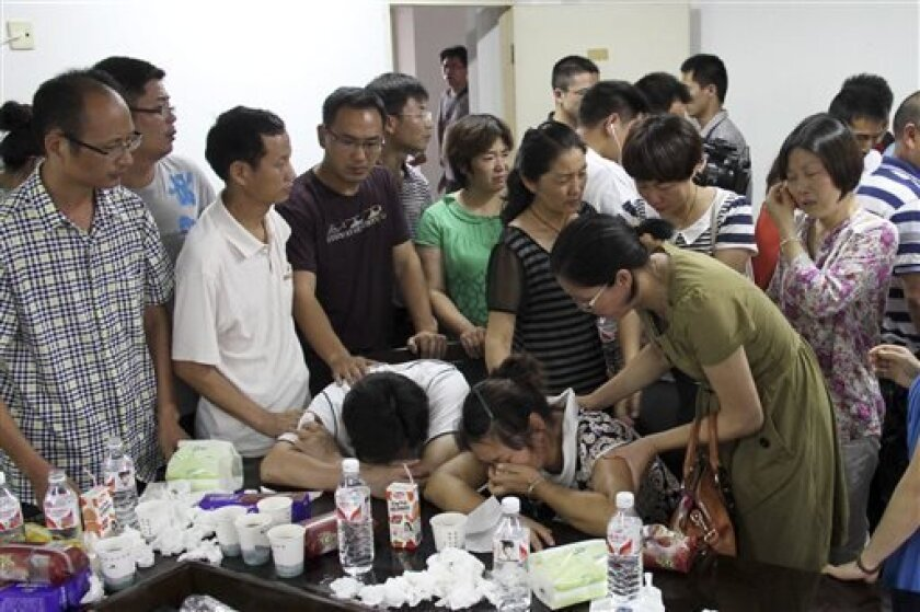 Parents of Wang Linjia, center, are comforted by parents of some other students who were on the Asiana Airlines Flight 214 that crashed at San Francisco International Airport, at Jiangshan Middle School in Jiangshan city, in eastern China's Zhejiang province, Sunday July 7, 2013. Chinese state media have identified the two people who died in the plane crash at San Francisco International Airport on Saturday as Ye Mengyuan and Wang Linjia, students at Jiangshan Middle School in China's eastern Zh