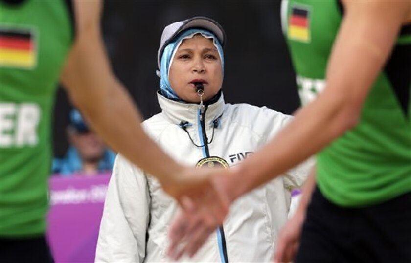 In this photo taken on Saturday, Aug. 4, 2012, Amina El Sergany of Egypt helps officiate a beach volleyball match at the 2012 Summer Olympics, in London. El Sergany is the first Muslim woman to referee the sport at the Olympics. While the bikini is the players' preferred uniform, El Sergany officiates the game wearing long pants with a hijab under her jacket, leaving only her face and hands uncovered. (AP Photo/Dave Martin)