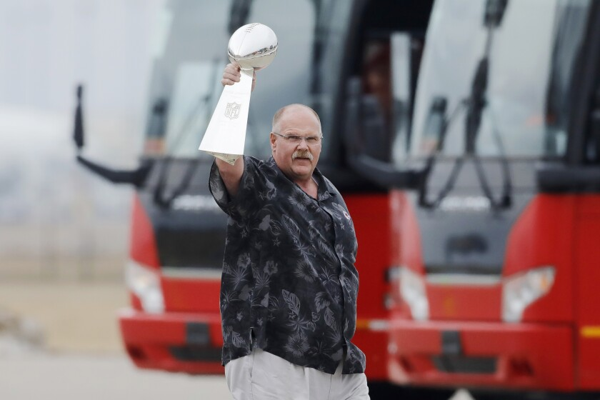 Sporting a Hawaiian shirt, coach Andy Reid hoists the Vince Lombardi Trophy after the Super Bowl champion Chiefs landed in Kansas City.