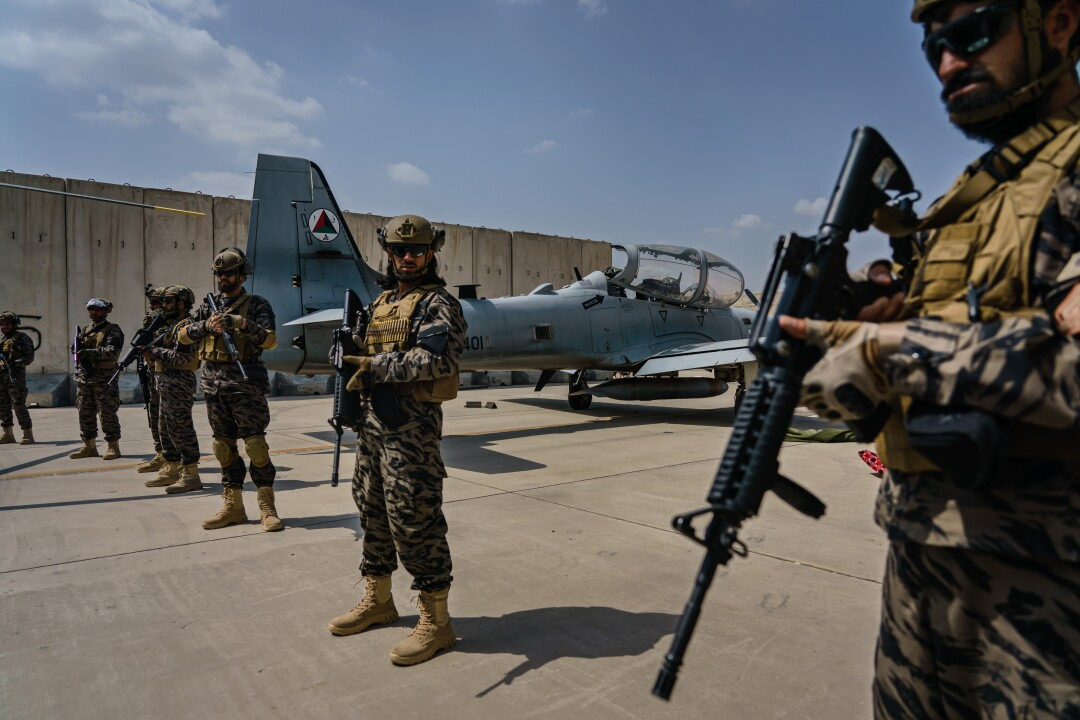 Taliban fighters stand with rifles in front of a military jet