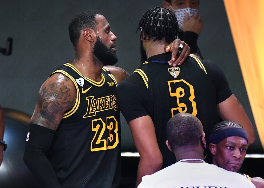 """The Lakers' LeBron James, left, talks with Anthony Davis after the Game 2 win over the Miami Heat in """"Black Mamba"""" jerseys."""