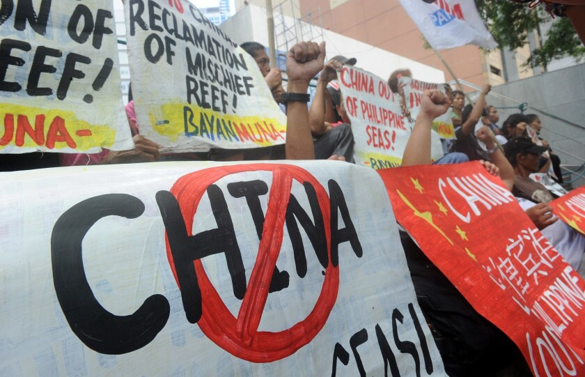 Filipino protesters display placards during a rally outside China's consular office in Manila on April 17 against the country's claim to islands and reefs in the South China Sea.
