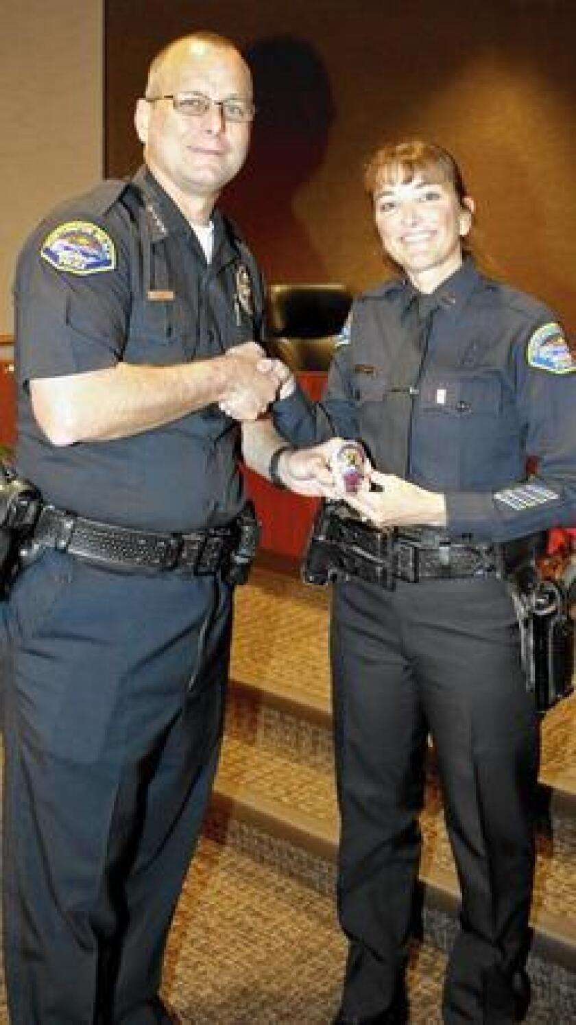 Kelly Rodríguez y el jefe Robert Handy posan con su nueva insignia de capitán. Rodríguez es la primera capitana en la historia del Departamento de Policía de Huntington Beach (Cortesía Policía de Huntington Beach).