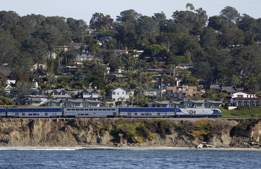 The Amtrak Surfliner train heads north along the tracks in Del Mar where bluffs toward the ocean regularly collapse on Dec. 5, 2019.