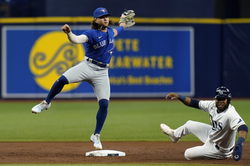 Toronto Blue Jays shortstop Bo Bichette forces Tampa Bay Rays' Manuel Margot, right, at second base and turns a double play on Kevin Kiermaier during the second inning of a baseball game Tuesday, Sept. 21, 2021, in St. Petersburg, Fla. (AP Photo/Chris O'Meara)