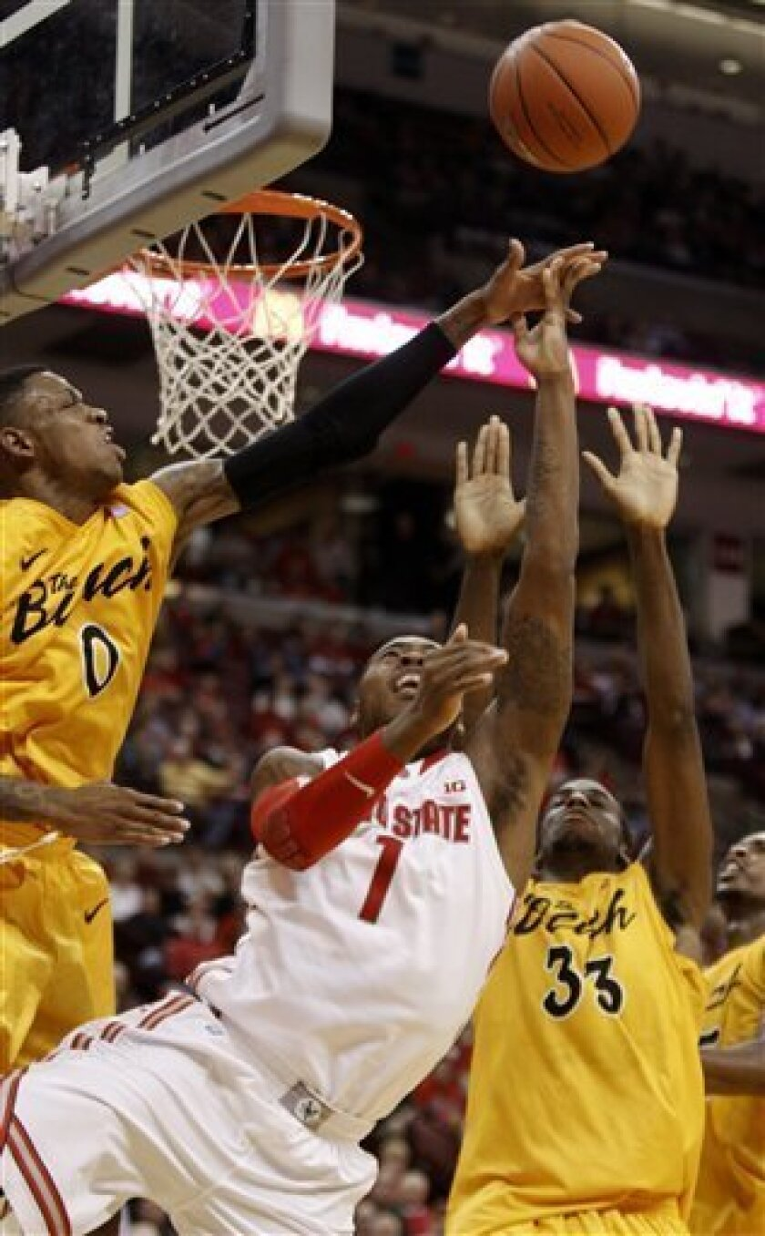 Ohio State's Deshaun Thomas, center, puts up a shot between Long Beach State's Kris Gulley, left, and Nick Shepherd during the first half of an NCAA college basketball game in Columbus, Ohio, Saturday, Dec. 8, 2012. (AP Photo/Paul Vernon)