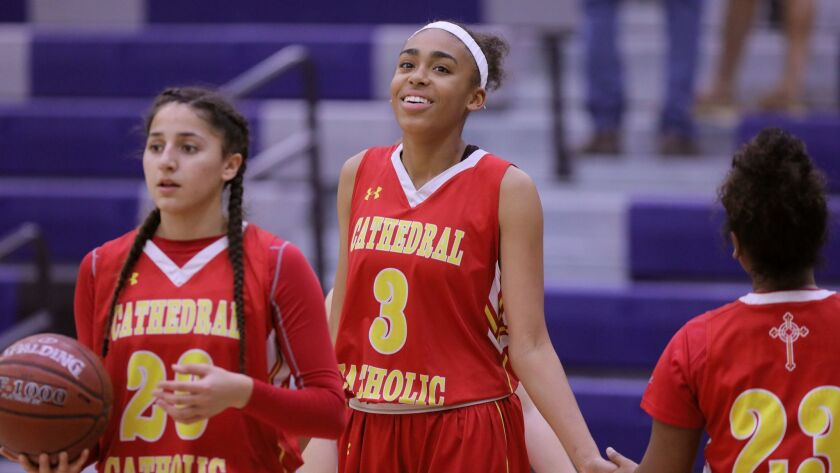Cathedtal Catholic's Mazatlan Harris, middle, greets a teammate during pre-game warmup. At left is Angelina Roque.