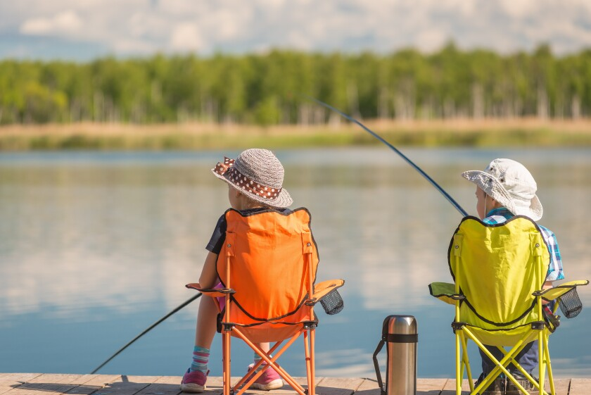 children with fishing rods sit on a wooden pier and fish at the lake