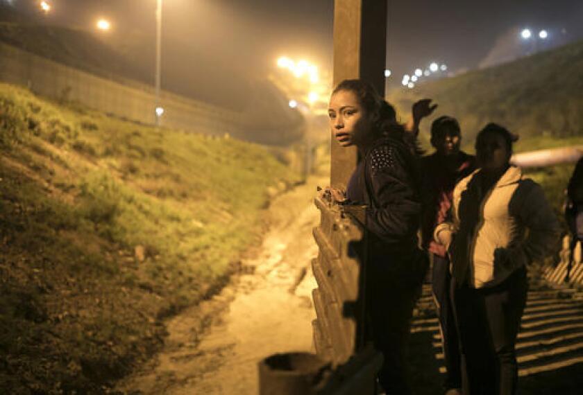 En esta imagen del 8 de febrero de 2019, la adolescente salvadoreña Xiomara Henríquez Ayala mira a la cerca fronteriza que separa Estados Unidos de Tijuana, México, buscando una forma para ayudar a sus acompañantes a cruzar sin ser detectados. (AP Foto/Emilio Espejel, archivo)