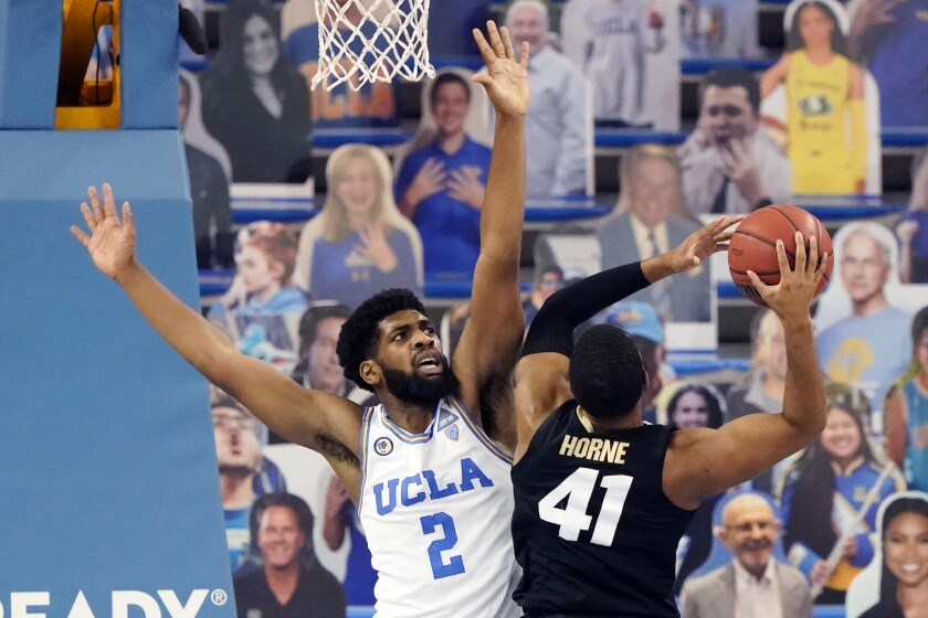 UCLA forward Cody Riley, left, defends on Colorado forward Jeriah Horne (41) during the second half of an NCAA college basketball game Saturday, Jan. 2, 2021, in Los Angeles. (AP Photo/Marcio Jose Sanchez)