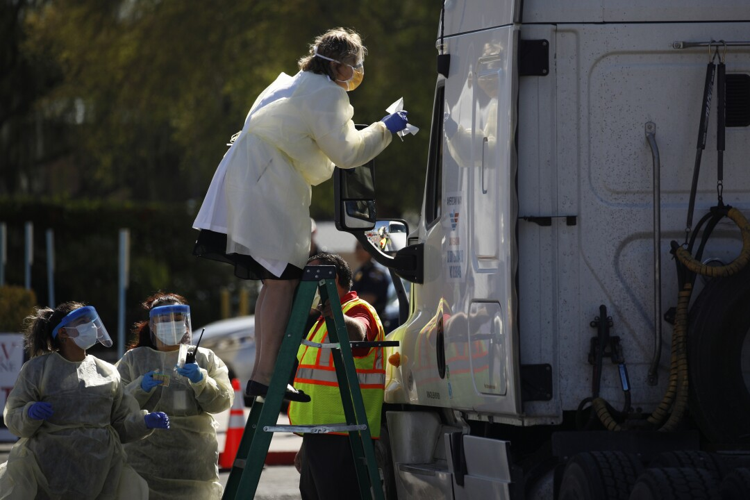 Dr. Elissa Palmer stands on a ladder to test a patient in a truck in Las Vegas.
