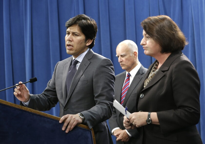 California state Senate President Pro Tem Kevin de León, left, accompanied by California Gov. Jerry Brown and Assembly Speaker Toni Atkins, announces he is scaling back a proposal to address climate change during a news conference on Wednesday in Sacramento.