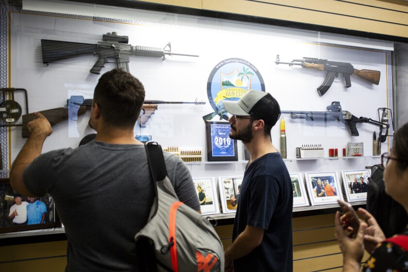 HONOLULU, HI - AUGUST 26: While waiting to pay for a shooting session, Oliver Girard, left, and Marc