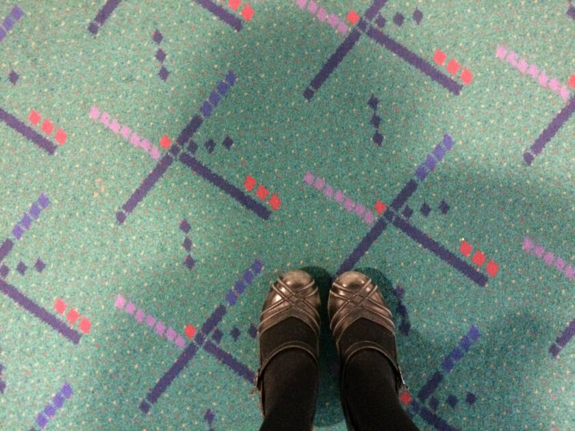 This selfie taken by Julie Sabatier Jan. 23, 2015, at Portland International Airport in Portland, Ore., shows her feet on older carpet due to be replaced at the terminal. After enduring three decades of luggage wheels and travel-worn passengers, the teal-color carpet is being replaced and as word spread that the carpet was going to be torn up it became an online and marketing superstar. (AP Photo/Rendered Podcast, Julie Sabatier)