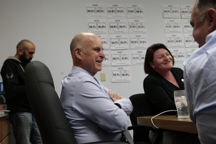 Relaxed after his easy victory over challenger Neel Kashkari, Gov. Jerry Brown checks the progress of state Democratic candidates at campaign headquarters with former Assembly Speaker John Perez, right, and current Speaker Toni Atkins.