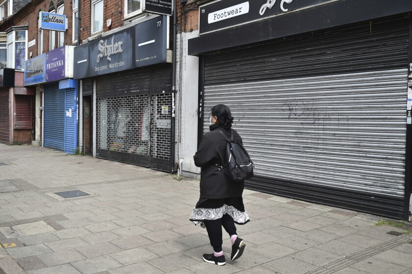 A woman walks past closes shops in Melton Road also known as the Golden Mile in Leicester, England, Tuesday June 30, 2020. The British government has reimposed lockdown restrictions in the English city of Leicester after a spike in coronavirus infections, including the closure of shops that don't sell essential goods and schools. (AP Photo/Rui Vieira)