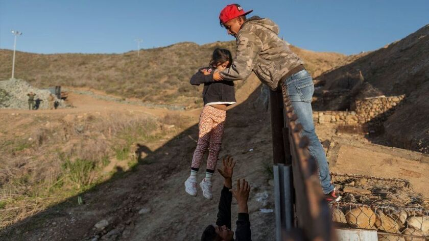 A migrant child from Honduras is passed to her father after he jumped the border fence to get into the United States from Tijuana on Jan. 3.