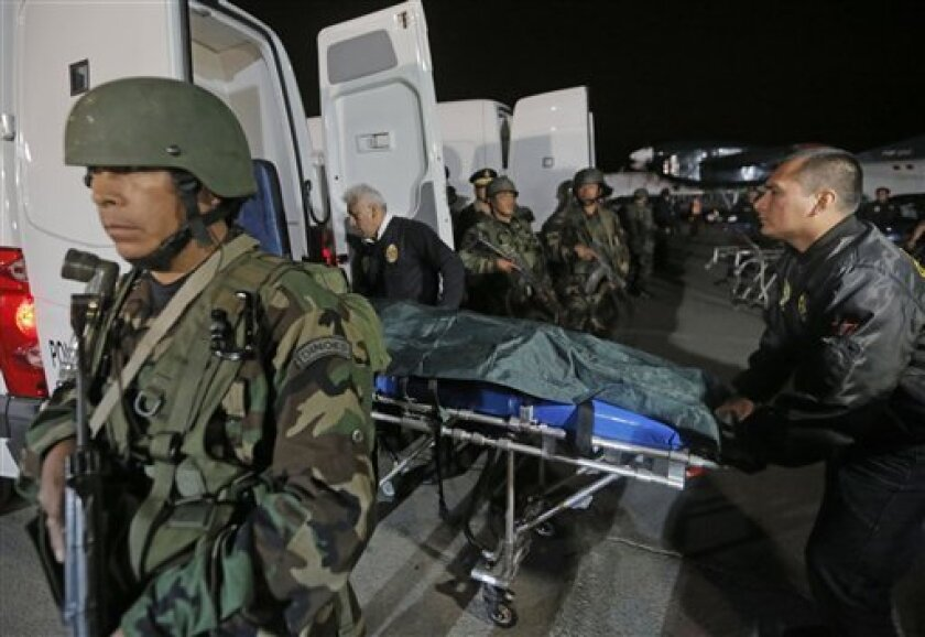 """In this photo released by Peru's Defense Minister, police officers stand guard during the arrive the bodies of two leaders of remains of the Shining Path rebel group at police base in Lima, Peru, Monday, Aug. 12, 2013. Peru's President Ollanta Humala tentatively identified them as """"Comrade Gabriel,"""" or Marco Antonio Quispe Palomino, the youngest of three brothers from the Quispe Palomino clan that commands an estimated 500 fighters, and """"Comrade Alipio"""" or Alejandro Borda Casafranca, the group's"""