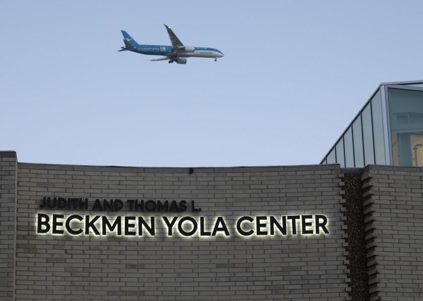 A plane flies over a building.