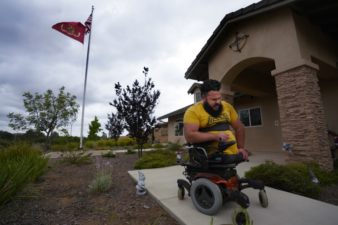 Jason Ross, who lost his legs while serving in Afghanistan, maneuvers in an automated wheelchair