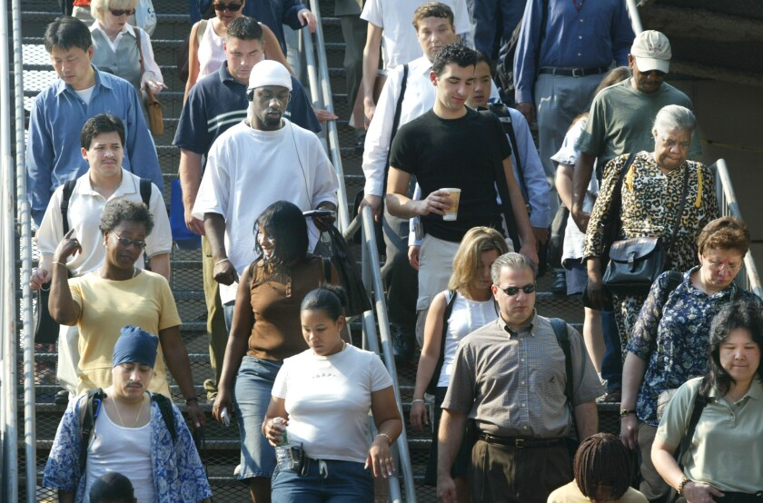 Commuters descend steps from the Staten Island Ferry on their way to work in New York City.