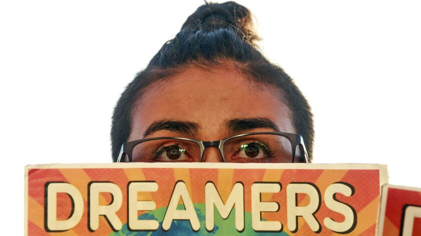 Alexis Torres holds a sign during a rally, put on by the San Diego Border Dreamers, marking the anniversary of the Trump Administration's attempt to end the DACA program at the County Administration Building in San Diego on Wednesday.