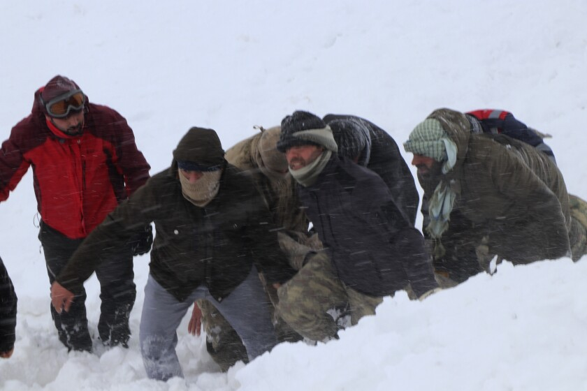 Emergency service members carry an avalanche victim near the town of Bahcesaray, Turkey, on Wednesday. An avalanche wiped out a team of rescue workers.